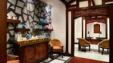 The spa hallway and welcome area features chairs, a product cabinet, desk and mosaic stone wall