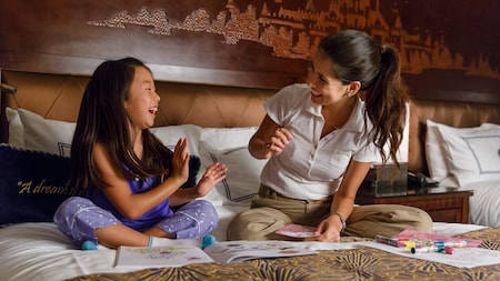 A mom and her young daughter laugh while sitting on their hotel bed doing coloring activities