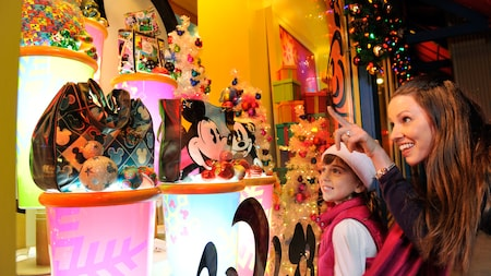 A woman and a girl look at Disney handbags and Christmas decorations