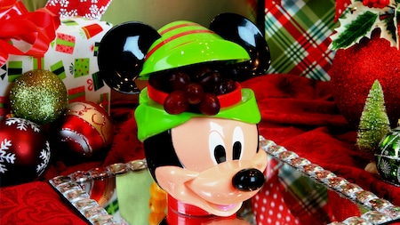 A holiday themed, Mickey Mouse fruit container overflowing with grapes