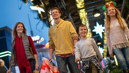 Two kids accompanied by their parents shop in the Downtown Disney District during the holiday season