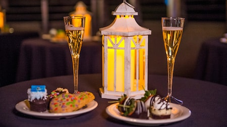 Bubbling flutes of champagne atop a table beside plates of dessert treats and a flickering lantern