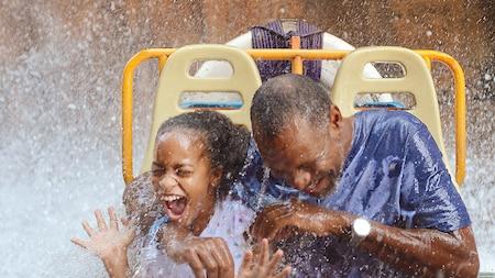 Une fille et son grand-père éclatent de rire alors qu'ils sont trempés à bord d'un manège d'un parc thématique