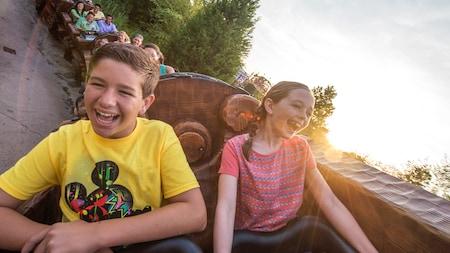 Un garçon et une fille rient à gorge déployée pendant une descente de montagnes russes d'un parc thématique