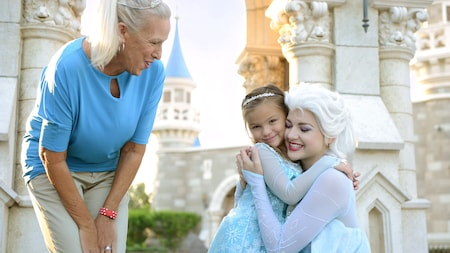 A grandmother smiles as Queen Elsa bends down to hug a little girl in front of Cinderella Castle