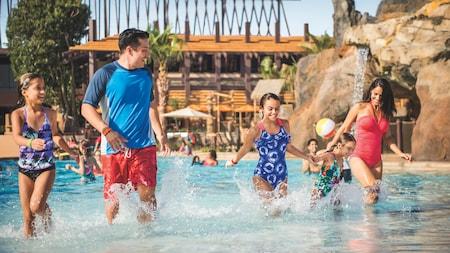 Une famille de 5 marche près d'une piscine sur le thème de la plage d'un hôtel Disney