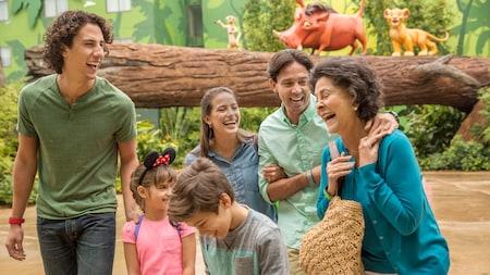 Une famille de 6 éclate de rire en passant devant une souche d'arbre horizontale où Timon, Pumba et Simba sont assis