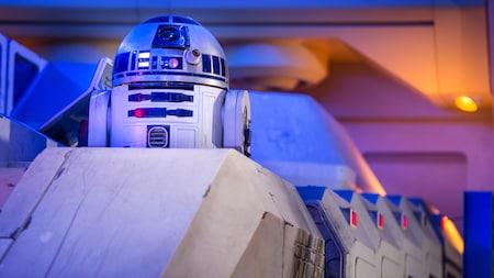 R2-D2 dépasse du vaisseau dans une pièce à l'éclairage impressionnant