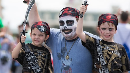 A father wearing skeleton makeup and a bandana and his son dressed as a pirate raise toy swords