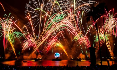 A glowing orb resembling the planet Earth floats across the World Showcase Lagoon at Walt Disney World Resort while a light and fireworks show is in progress overhead