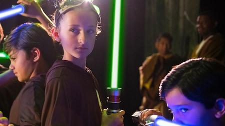 Tres jóvenes Jedi empuñan sables de luz