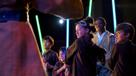 Three young Jedi holding lightsabers while a Jedi Master looks on