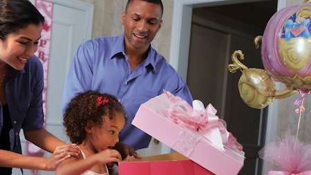 A little girl is surprised when she opens a big present, with her delighted parents looking on