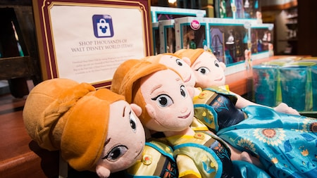 Plush dolls in a store with a sign reading 'Shop Thousands of Walt Disney World Items'