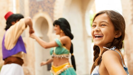 A girl laughs with delight to see Jasmine and Aladdin dancing