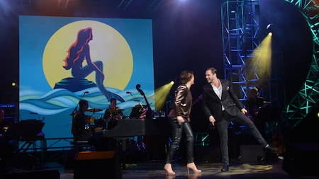 2 people dance on stage in front of a band and a picture of Ariel sitting on a rock in the ocean