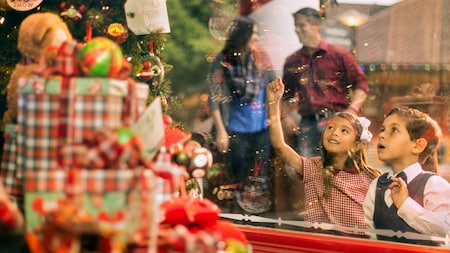 2 young children look in awe at a decorated Christmas tree on display in a shop window