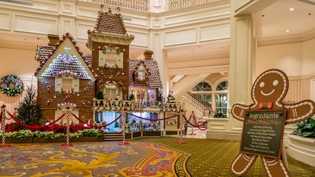 An almost-life-sized decorated gingerbread house stands inside a hotel lobby