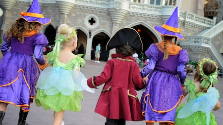 Quatre enfants costumés se rendent au Mickey's Not-So-Scary Halloween Party