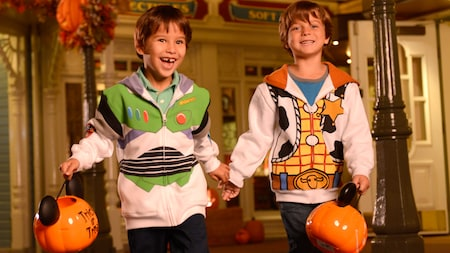 Young male Guests in Buzz Lightyear and Woody sweatshirts trick-or-treating on Main Street, U.S.A.