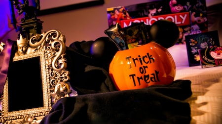 A Mickey inspired jack o lantern basket filled with Disney treats sits next to a framed mirror with an Evil Queen motif and in front of a Disney themed Monopoly game