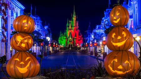 Main Street, USA at night during Mickeys Not So Scary Halloween Party, featuring autumn leaves and jack o lantern decor
