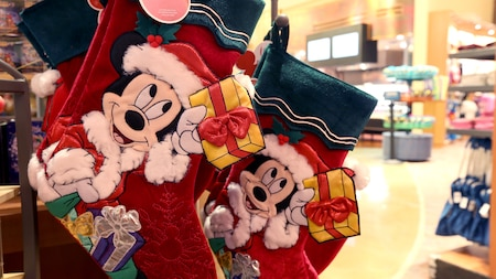 Holiday stockings featuring Mickey Mouse as Santa Claus hang from a shelf inside a theme-park shop
