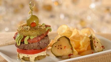 Una minihamburguesa de calabacín frito, tomates, jamón, hamburguesa de carne de res, salsa y una aceituna, cerca de pepinillos y chips de papas