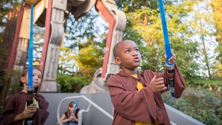 Visitantes jóvenes vestidos como caballeros Jedi sostienen sables de luz afuera de Star Tours – The Adventures Continue