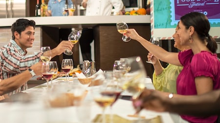 Guests sitting across from one another at a table look on excitedly while aerating glasses of wine