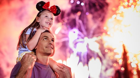 A young girl in Minnie Mouse ears with a bow sits atop her father's shoulders
