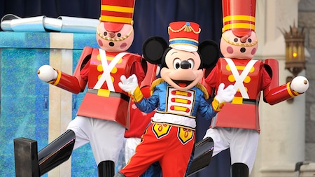 Mickey dressed in seasonal holiday clothing dancing in formation between two life-size nutcrackers