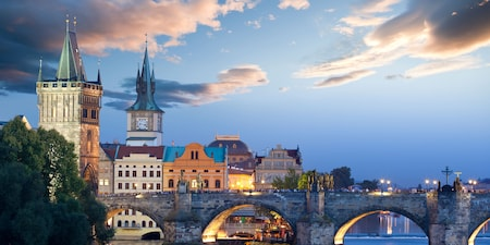 The Charles Bridge is lined with pedestrians and bordered by cathedral towers and other buildings