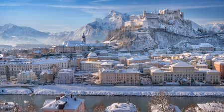 Picturesque Salzburg with snow covering the streets, buildings and surrounding mountains