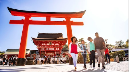 A family of 4 walks past the torii gate in front of Fushimi Inari Shrine in Kyoto, Japan