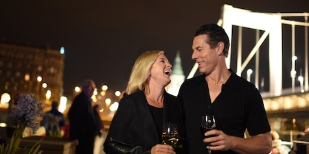 A man and a woman stand on a ship's deck at night, drinking wine and laughing
