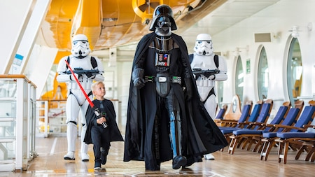 A young boy wearing a Darth Vader ensemble sans mask walks alongside the Dark Lord himself as Stormtroopers loom a few paces behind them