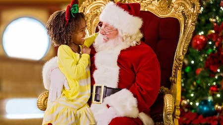 A small girls sits on Santa's lap and smiles while looking into his eyes