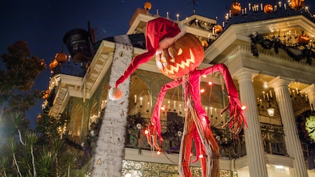 A jack o lantern scarecrow wearing a Santa hat stands next to the Haunted Mansion decorated with candles and pumpkins