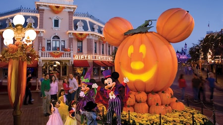 Mickey and Minnie Mouse stand with 3 small girls dressed as princesses next to an oversized Mickey inspired jack o lantern on Main Street, U.S.A.