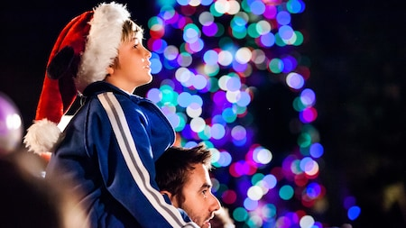 A Santa-capped boy sits on his dad's shoulders to watch the parade, part of the Holiday Time at Disneyland Tour