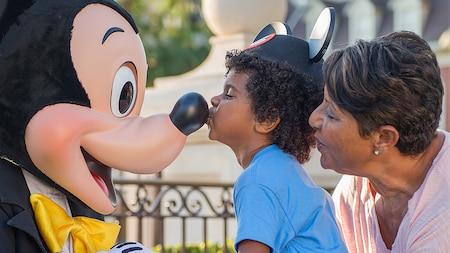 Un petit garçon embrasse Mickey Mouse sur le nez tandis que sa grand-mère regarde