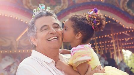 Le PrinceCharmingRegalCarrousel tourne alors qu'une petite fille embrasse son grand-père sur la joue