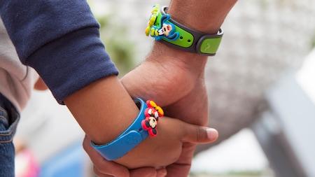 Un grand-père et un petit-fils se tiennent la main avec des bracelets de couleurs vives MagicBand à thème de Disney.