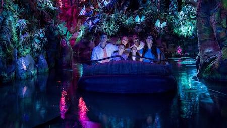 Des visiteurs regardent autour d'eux avec émerveillement en flottant dans une forêt bioluminescente à bord de Na'vi River Journey