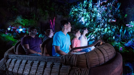 Guests Enjoying The Bioluminescence Of Navi River Journey While They Ride Aboard A Woven
