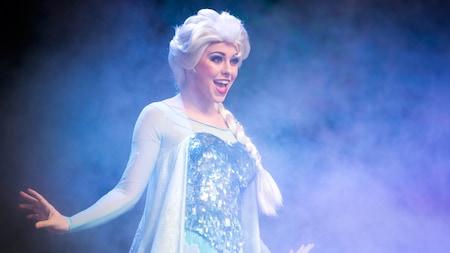 A rainha Elsa canta no palco, cercada por um nevoeiro gelado