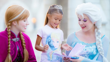 A little girl with a tiara and an Elsa shirt gets autographs from the real Anna and Elsa