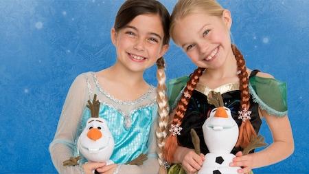 Duas meninas vestidas como Anna e Elsa seguram bonecos de pelúcia do Olaf