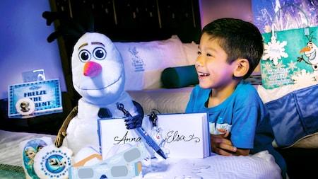 Um menino olha para seus presentes de Frozen: Uma Aventura Congelante, incluindo um Olaf de pelúcia e um livro de autógrafos assinado pela Anna e pela Elsa